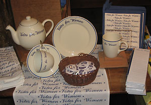 "Tea Set. In the days before the 19th Amendment, a wealthy Newport socialite ordered a tea set emblazoned with the phrase ""Votes for Women"" to make a point to the influential guests who often dined with her. The Alcotts were ardent supporters of the women's suffrage movement, and today we offer replicas of this tea set and other items bearing the ""Votes for Women"" motto."